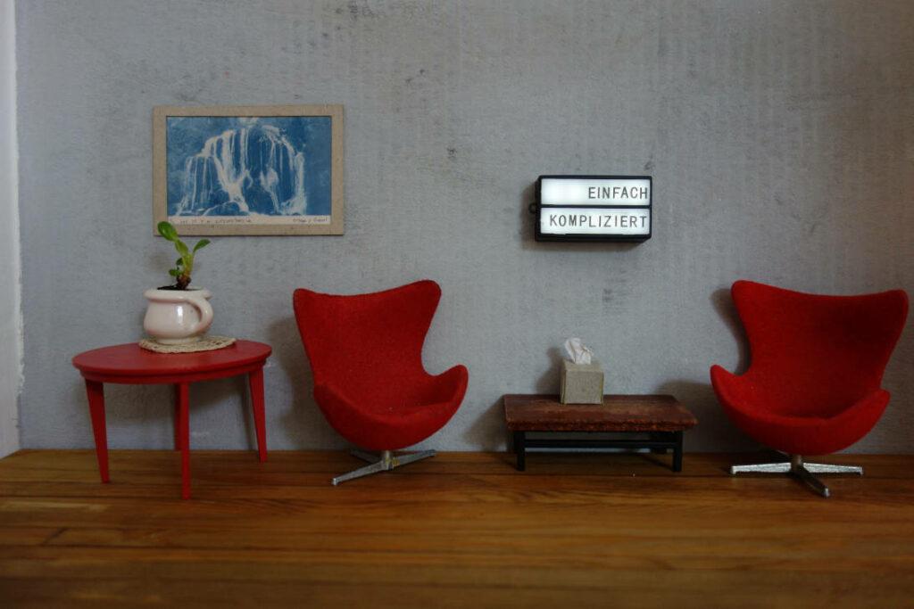 ein roter Tisch, ein Bild, zwei rote Sessel